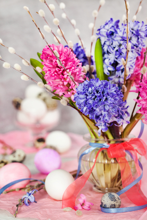 Easter eggs with beautiful hyacinths and willow bouquet on light background, spring holiday concept Banque d'images