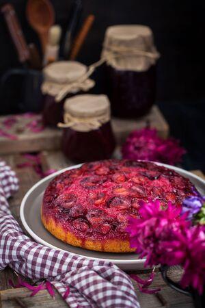 Fresh homemade upside-down plum cake on rustic background