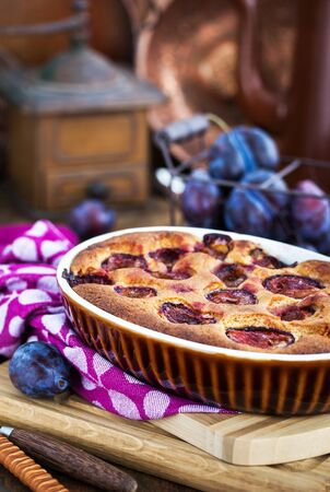 Fresh homemade dimply plum cake on rustic background