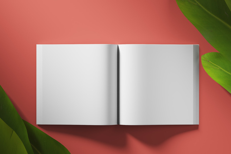 Empty white book unfolded on red background with tropical flowers. Top view. Mock up. Stockfoto