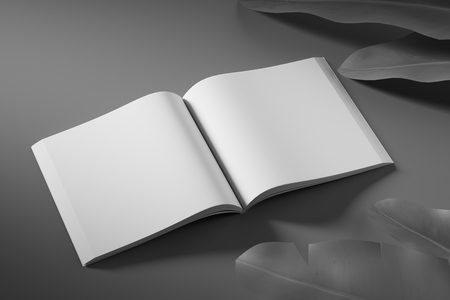 Side view of an empty white unfolded book on a black background with tropical flowers. Mock up.