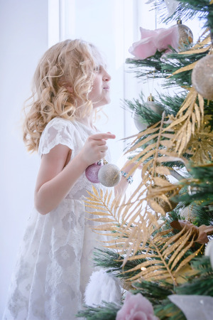 Children Waiting for the New Year and Christmas. Cute little girl decorating christmas tree by baubles at home.