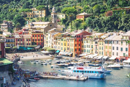 Portofino, Liguria, Italy: 09 august 2018. Portofino landscape, best touristic Mediterranean place with colorful houses, fishing boats and luxury yacht, picturesque harbor.