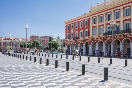 Zentraler Platz in Nizza, Provance_Alpes-Côte d'Azur, Französisch, 15. August 2018; Ein Blick auf den Platz Massena mit Straßenbahnschienen, roten Häusern und Straßenlaternen. Editorial