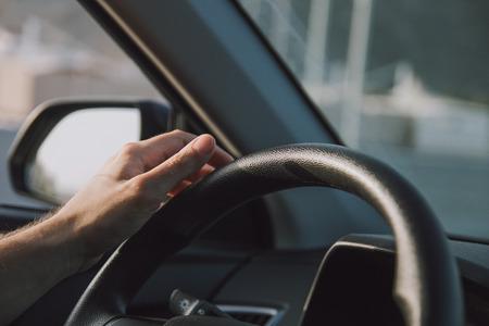 Jonge mensenhand die het autostuurwiel houden Stockfoto