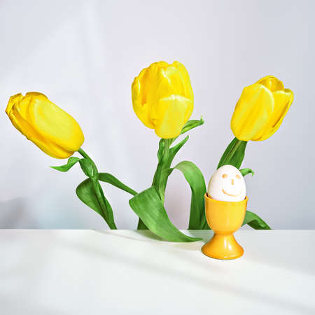 spring yellow flowers, tulip bouquet and easter egg in yellow stand, square