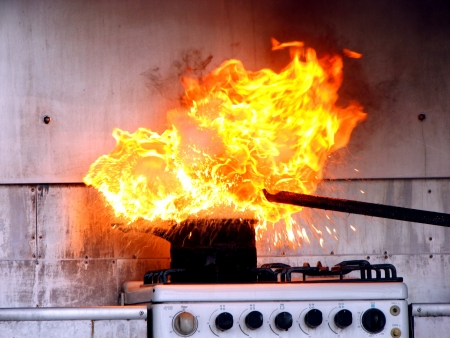 kitchen: Putting water on oil fire on stove Stock Photo