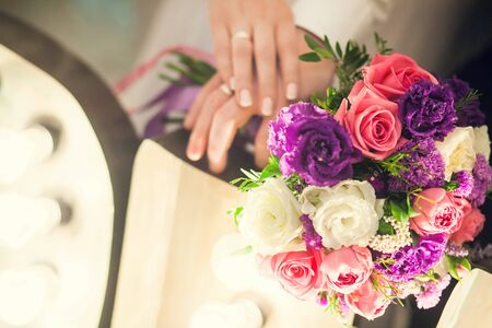Wedding bridal bouquet on the background of the hands of the newlyweds.