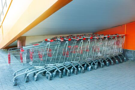 Many metal shopping carts on a parking lot near supermarket outdoors, standing under the stairs