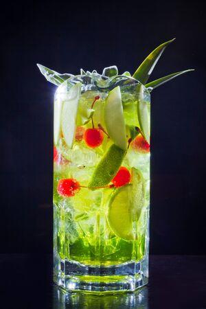 绿色饮料鸡尾酒用苹果,石灰和樱桃在大公司的大瓶子,在黑背景隔绝的特写镜头。