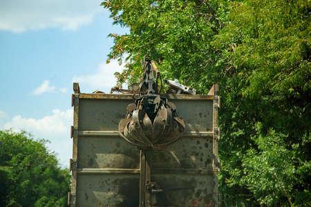 Truck with hydraulic manipulator for collecting and transporting scrap metal. Crane grab scrap. Foto de archivo