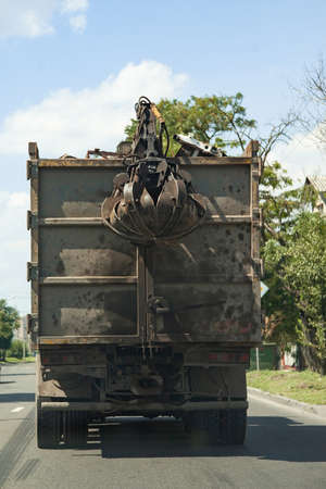 Grapple truck unloads scrap industrial metal for recycling. Manipulator with hydraulic magnet crab against sky. Crane garbage truck loading industry waste. Crane grab scrap.