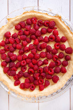 Preparation of shortbread pie with raspberries on a white wooden background, top view.