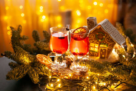 Christmas drink with spicy and berries. Cozy still Life with glasses, gingerbread house and spruce branches. Stock fotó