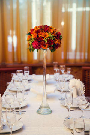 Autumn bouquet of flowers decorates the festive table in the restaurant.