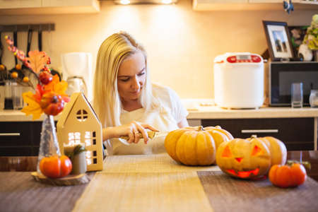 Woman on kitchen carves a pumpkin for Halloween in a room with autumn decor and a lamp house. Cozy home and preparing for Halloween. Reklamní fotografie