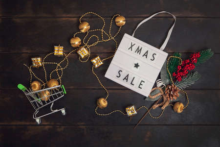 Xmass Sale word on lightbox and small shopping cart with golden gifts on wooden background.