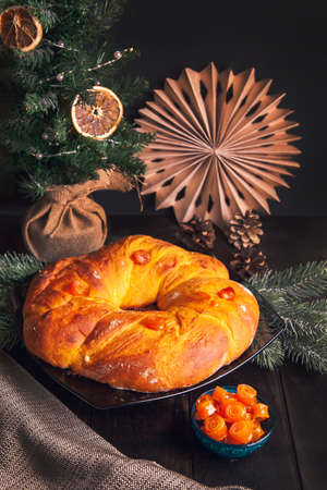 Home baked Christmas bread in a shape of Advent wreath of yeast dough with orange candied fruits on background of Christmas tree. Imagens