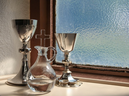 old items: Holy communion items inside a church sacristy with a blue, lead glass window in the background Stock Photo