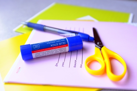 writing utensil: A glue-stick, scissors and a pen lying on a copy-book Stock Photo