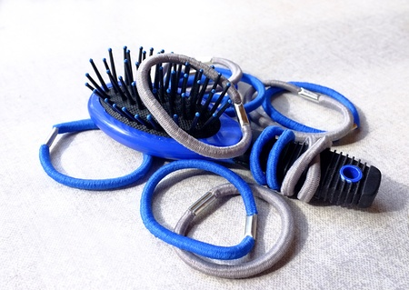 scrunchy: A few simple blue and gray elastic hair bands and a small hair-brush Stock Photo