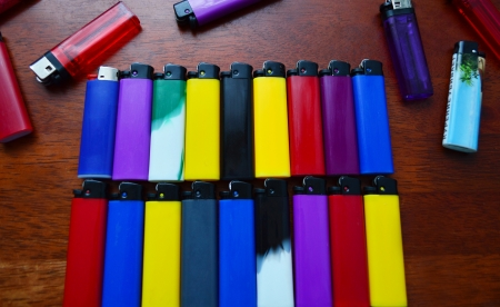 Colored lighters lying in two rows on a table Stock Photo - 24723997