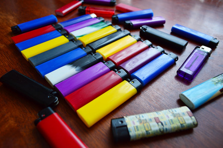 Colored lighters lying in two rows on a table Stock Photo - 27540793