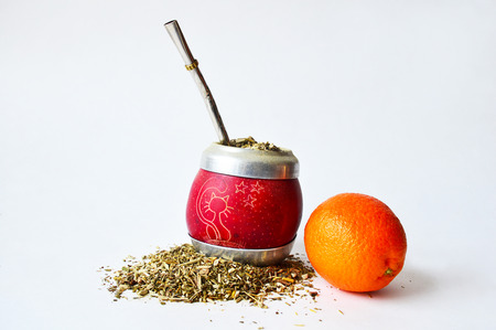 pictured: Pictured hand-made mate cup of a small pumpkin full of guarana with some spilled out. Metallic tube for drinking and a mandarin Stock Photo
