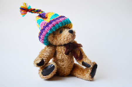 stocking cap: Toy teddy-bear wearing a striped bobble cap