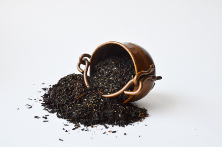 Overturned three-leg copper pot with half-spilled black tea Stock fotó