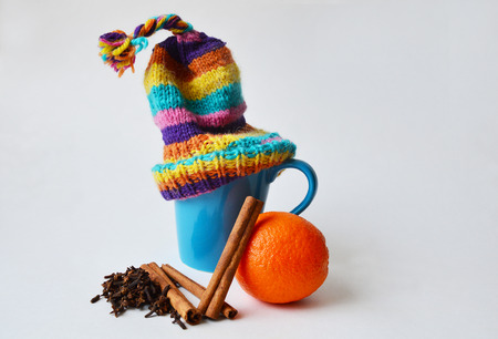 stocking cap: Blue cup wearing a bobble knitted striped hat, orange, cinnamon sticks and cloves