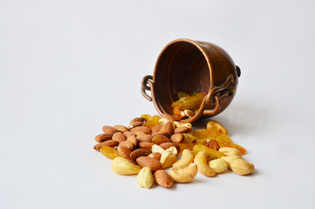 Overturned three-leg copper pot with nuts and raisins