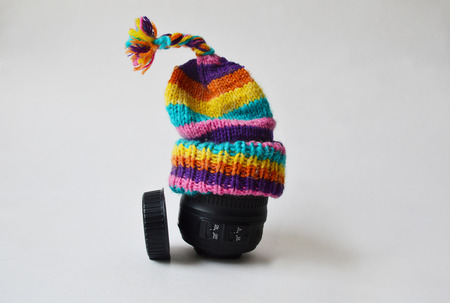 bobble: Lens wearing a bobble knitted striped hat against condensation and a lens cap near it