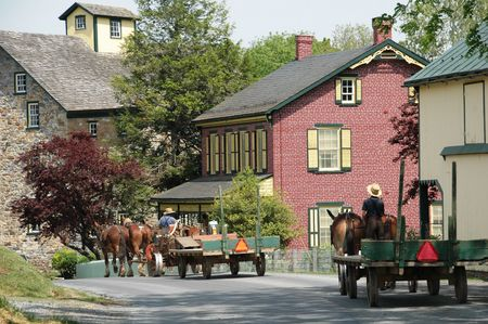 amish buggy: Amish farm wagon teams on road in Pennsylvania Stock Photo
