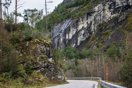 Mountains cloudy road in scandinavia nature travel. View on rocks and forest hills with foggy cloudy sky. Northern landscape driving way background. Archivio Fotografico
