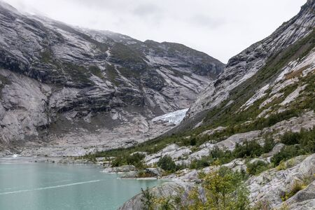 Norway mountains landscape view near lake with azure blue water, rocks, glacier, snow. Cloudy day tracking trip to Nigardsbreen in Jostedalsbreen national park
