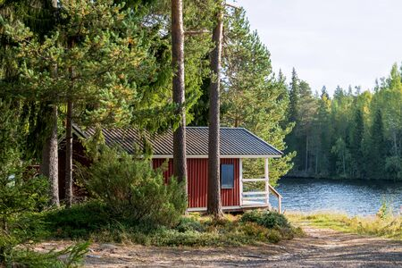 Red wooden finnish traditional cabins cottages in green pine forest near river. Rural architecture of northern Europe. Wooden houses in camping on sunny summer day