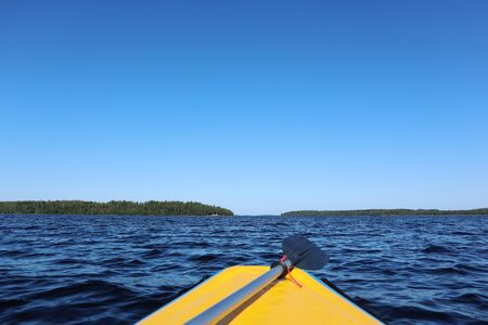Rafting adventure first person view from yellow boat with paddle on finish lake bright sunny day blue water windy