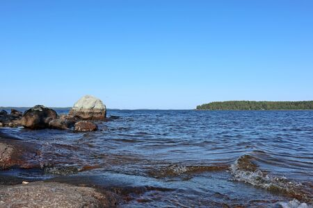 Stones granite coast of island on finnish lake on bright sunny summer day blue sky and water landscape view scenic nature background
