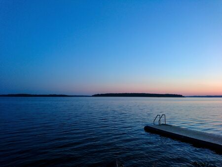 Sunset sky on lake in Finland calm coast water blue vibrant sky background