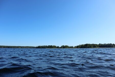 Blue water clear sky sunny day on finnish lake water waves close up. Beauty of nature skyline and forest with deep colored water. Photo from boat