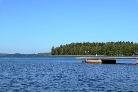 Wooden swimming dock pier with metal ladder on calm blue lake sunny day on nature Finland idyllic natural resort