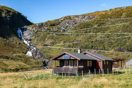 Norwegian traditional rural village black house with solar panels on serpentine mountain road on hill, waterfall distance view. Autumn drive scandinavia Myrkdalsvegen Serpentinveg, Sendefossen