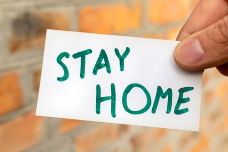 Stay home words on white card holding in hand on sunny red brick wall background. Prevention contamination virus risk safety isolation stay info note Stockfoto