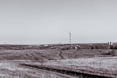 Greyscale field and heat power station pipe with stripes on horizon. Europe, Ukraine countryside, clear sky landscape with air pollution smoke tower.