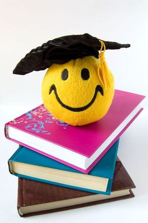 Happy grad toy in a black cap on a pile of books photo