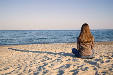 blue sky thinking: A young woman sitting alone at the seaside
