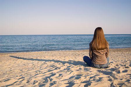 mujer mirando el horizonte: Una joven mujer sentada sola en la playa