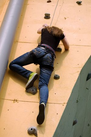 strive for: A girl climbing persistently to the top of the wall