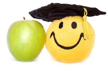 morter: Happy giocattolo grad in una tavola Morter con una mela verde, isolato su uno sfondo bianco